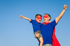 Père et fils jouant le super héros au temps de jour Image stock