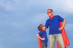 Père et fils jouant le super héros au temps de jour Images stock