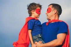 Père et fils jouant le super héros dehors au temps de jour Image stock
