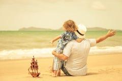 Père et fils jouant sur la plage au temps de jour Image stock