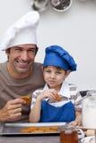 Père et fils mangeant des biscuits dans la cuisine image stock