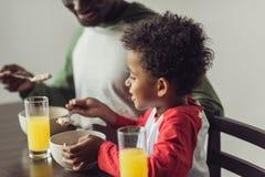 Père et fils mangeant le petit déjeuner Photographie stock libre de droits