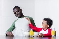 Père et fils mangeant le petit déjeuner Images stock