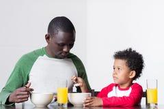 Père et fils mangeant le petit déjeuner Photos stock