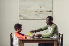 Père et fils mangeant le petit déjeuner Photo stock
