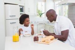 Père et fils mangeant un petit déjeuner Photographie stock