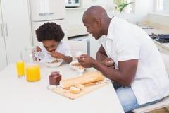 Père et fils mangeant un petit déjeuner Images libres de droits