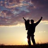 Père et fils marchant sur le champ au temps de coucher du soleil Image libre de droits