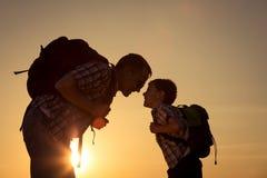 Père et fils marchant sur le champ au temps de coucher du soleil Photo stock