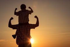 Père et fils marchant sur le champ au temps de coucher du soleil Photos libres de droits