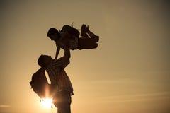 Père et fils marchant sur le champ au temps de coucher du soleil Photos stock