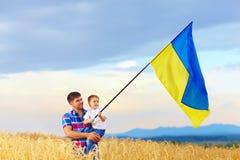 Père et fils ondulant le drapeau ukrainien sur le champ de blé Images stock