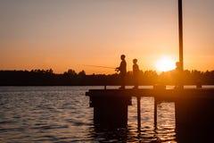 Père et fils pêchant en rivière au coucher du soleil, silhouette image stock
