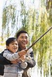 Père et fils pêchant ensemble au lac Images libres de droits