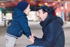 Père et fils parlant entre eux tenant des mains regardant l'un l'autre Photo libre de droits