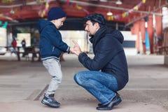 Père et fils parlant entre eux tenant des mains regardant l'un l'autre Images stock