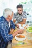 Père et fils parlant entre eux tout en prenant le petit déjeuner Photos stock