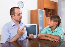 Père et fils parlant sérieusement à la maison Image stock