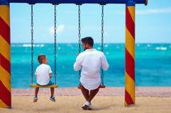 Père et fils parlant sur des oscillations sur la plage Image libre de droits