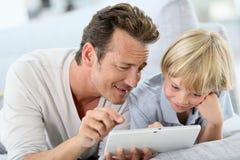 Père et fils passant le bon temps jouant avec le comprimé Image libre de droits