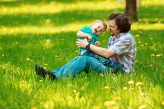 Père et fils passant le temps ensemble un jour ensoleillé Litt heureux photographie stock libre de droits