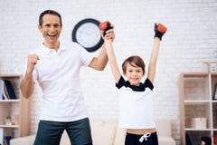 Père et fils posant sur la caméra dans des gants de boxe photos libres de droits