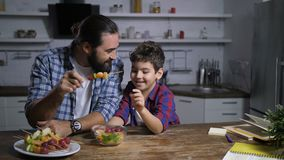 Père et fils préparant des brochettes de fruit dans la cuisine banque de vidéos