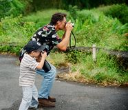 Père et fils prenant des photos Images libres de droits