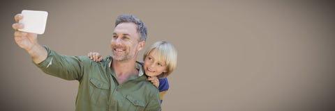 Père et fils prenant le selfie sur le fond brun Photographie stock