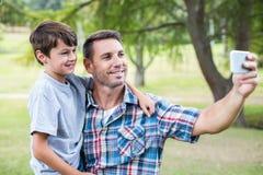 Père et fils prenant un selfie en parc Photos libres de droits