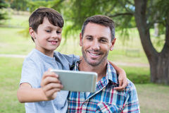 Père et fils prenant un selfie en parc Images stock