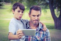 Père et fils prenant un selfie en parc Photographie stock