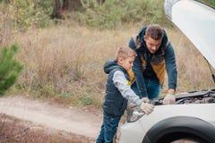 père et fils réparant le moteur de voiture ensemble images libres de droits