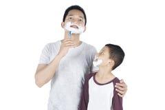 Père et fils rasant la barbe sur le studio Photo libre de droits