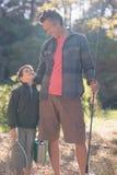 Père et fils regardant l'un l'autre avec l'équipement de pêche Photos libres de droits