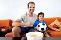 Père et fils regardant la TV ensemble Photographie stock