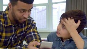 Père et fils regardant le smartphone banque de vidéos