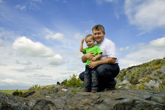 Père et fils restant au bord de la roche Photos libres de droits
