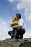 Père et fils restant au bord de la roche Photo stock