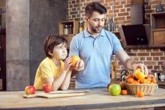 Père et fils sélectionnant des fruits de panier images libres de droits