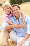Père et fils s'asseyant sur des balles de paille dans moissonné Images stock