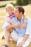 Père et fils s'asseyant sur des balles de paille dans moissonné Photographie stock libre de droits