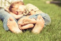 Père et fils s'asseyant sur l'herbe au temps de jour Images libres de droits