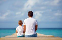 Père et fils s'asseyant sur la jetée près de la mer images stock