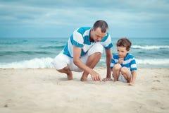 Père et fils s'asseyant sur la mer photo libre de droits