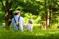 Père et fils s'asseyant sur la pelouse de forêt Photographie stock libre de droits