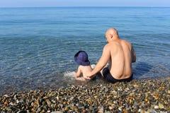 Père et fils s'asseyant sur le bord de la mer Image libre de droits