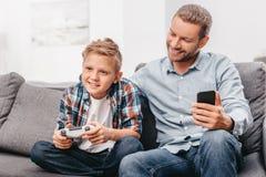 Père et fils s'asseyant sur le divan dans le salon tandis que le fils joue des jeux vidéo photographie stock