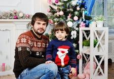 Père et fils s'asseyant sur le fond de l'arbre de Noël Photos stock