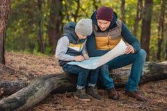 père et fils s'asseyant sur le rondin et regardant la carte photos stock